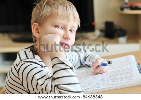 left-handed boy doing a boring home task at home - stock photo