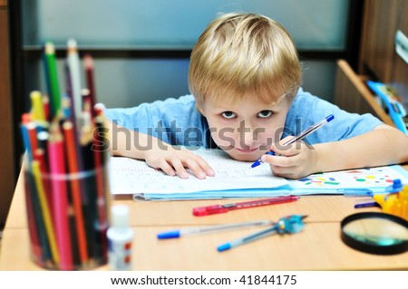 left-handed boy doing a home task in own room - stock photo