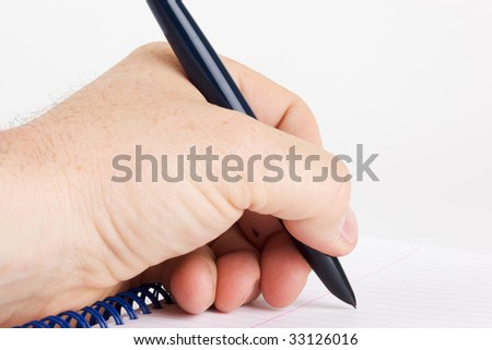 Left handed writer writing on a spiral notebook designed for right handers. - stock photo