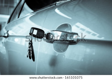 Left key on the car door at parking lots - stock photo