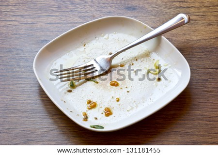 left over food on wooden table with fork - stock photo