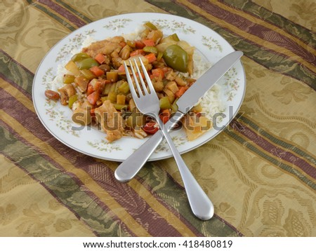 Left over take out Kung Pao Chicken meal on plate with knife and fork on tablecloth - stock photo