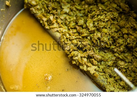 Left-Overs of Hops and Essential Oils of the mash into a Stock Pot after the Home Brewing Process - stock photo