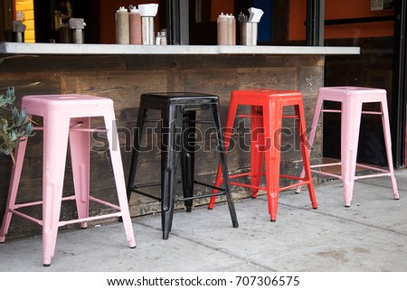 left side of a row of red and pink square bar stools below a counter with