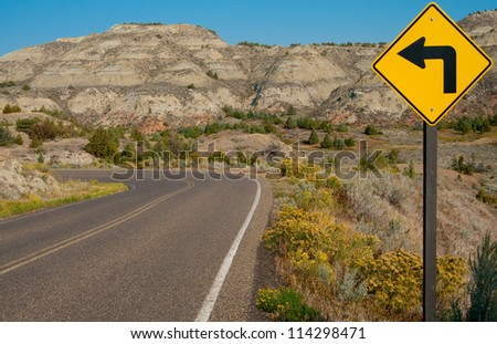 Left Turn Sign:  A road sign warns of a sharp left turn on a narrow road through Theodore Roosevelt National Park in southwest North Dakota. - stock photo