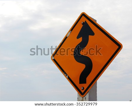 Left Winding Road, traffic sign on nature background        - stock photo
