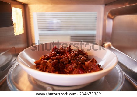 Leftover Chili Cooking Inside Microwave Oven - stock photo