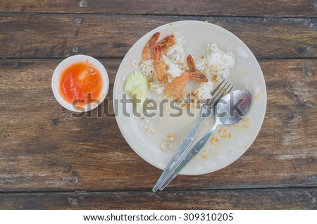 Leftover food on place after breakfast over wood texture background. - stock photo
