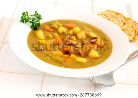 Leftover ham bone slow simmered, chock filled with root vegetables make for a delicious healthy soup - stock photo