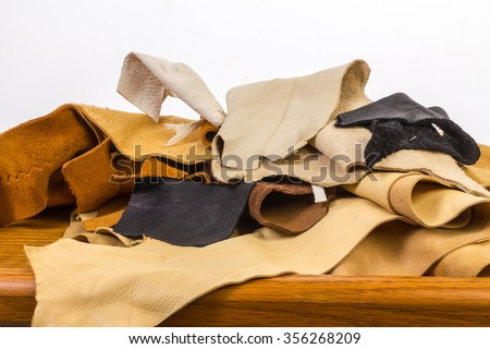 Leftover pieces of rawhide; buckskin; doeskin; leather; cow hide and suede on old wooden work bench against white background with copy space.