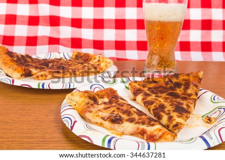 Leftover pizza reheated and served on paper plates with cold beer.  Red plaid background to emphasize ethnicity. - stock photo