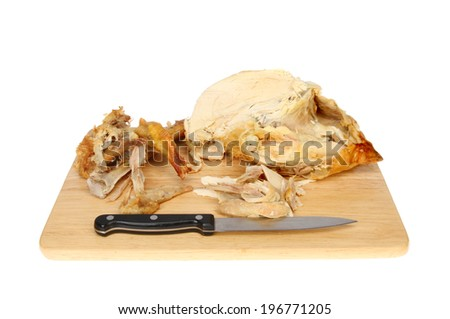 Leftover roast chicken with a knife on a wooden board isolated against white - stock photo