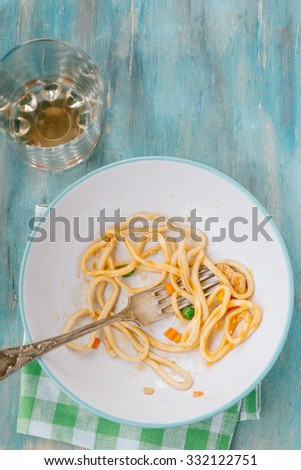 Leftovers of noodles with vegetables in bowl on a wooden background Top view - stock photo