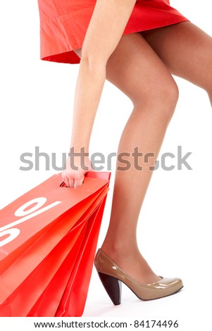 Leg and arm of lady carrying red paper bags - stock photo