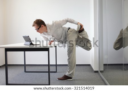 leg exercise during office work - standing man reading at tablet in his office - stock photo