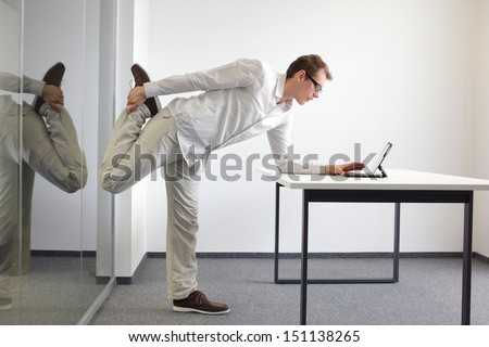 leg exercise durrng office work - standing man reading at tablet in his office - stock photo