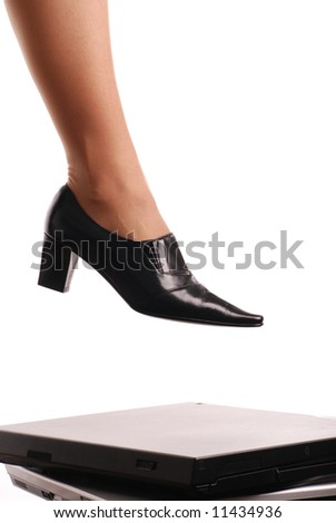 Leg of woman in elegant shoe stepping on computers - isolated on white background - stock photo