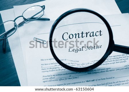 legal contract with magnifying glass and glasses - stock photo