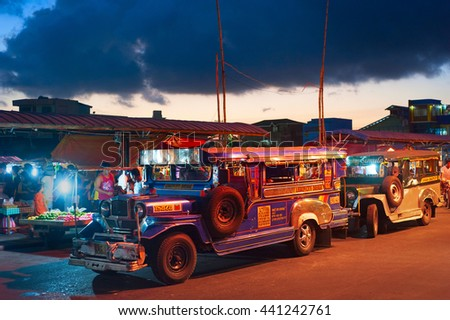 LEGAZPI, PHILIPPINES - APRIL 07, 2012:  Jeepneys waiting for passengers on the street. Jeepneys are public transport. They were originally made from US military jeeps left over from World War II. - stock photo