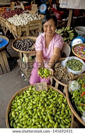 LEGAZPI, PHILIPPINES - NOVEMBER 17, 2012 - Unidentified Filipino woman selling Cucumber Tree Fruit on November 17, 2012 at Legazpi, Philippines. Averrhoa Bilimbi is used as an herbal medicine. - stock photo