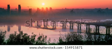 Legendary metal bridge Paton at dawn, amid new quarters, symbolizes the new and the old town. Morning fog creeps over the beautiful River of the legendary Ukrainian. Fabulous spectacle for human - stock photo