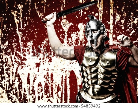 Legionary soldier over abstract bloody wall - stock photo