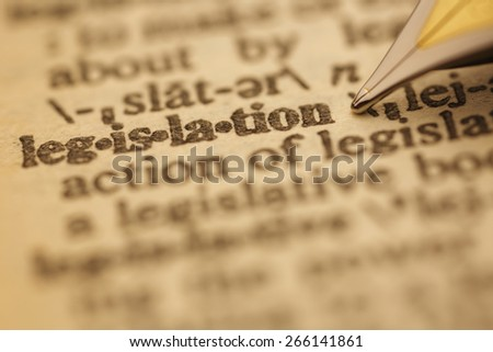 Legislation pen nib pointing to the words in the dictionary, shot with very shallow depth of field, - stock photo