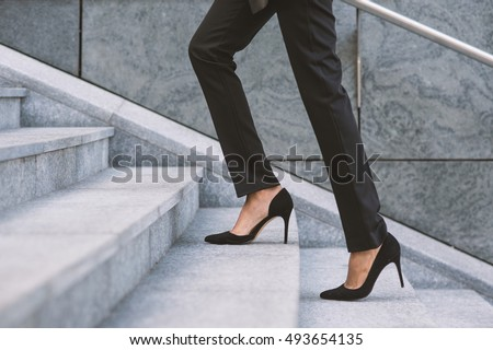 Legs and feet detail of businesswoman climbing stairs outdoors in Milan.