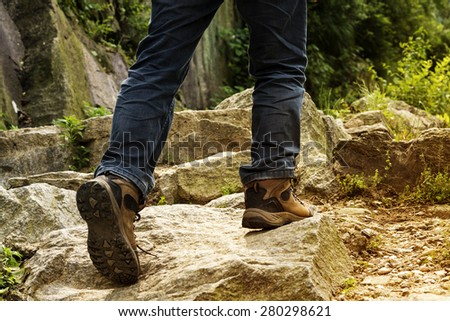 Legs and feet of a male hiker climbing up a mountain trail  - stock photo