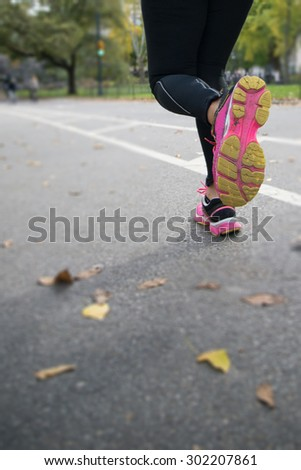 Legs and feet of a woman wearing log exercise leggings running t - stock photo