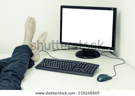 legs and feet without shoes on desk with white screen - stock photo