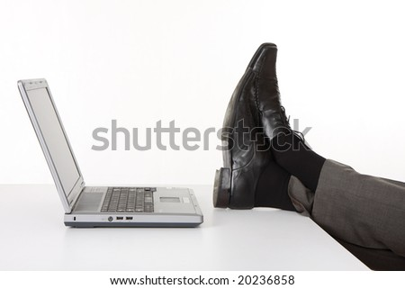 legs and laptop on  the desk