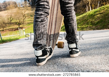 Legs and sneakers of a young boy and an edgewise longboard - stock photo