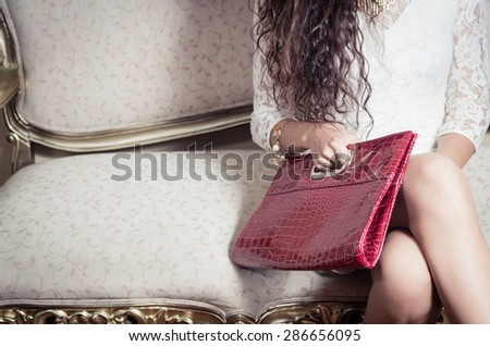 legs and torso of model girl sitting on victorian sofa holding a red purse with right hand - stock photo
