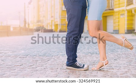 Legs close up. Fashion summer of hipster couple. Close up of feet. Man and woman posing on the city street. Blue dress woman. Man's sneakers and denim. Woman standing on tiptoe try to kiss man. Love.