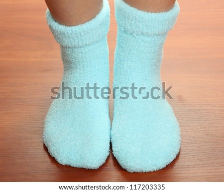 Legs female in blue socks on laminate floor