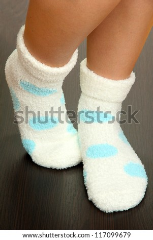 Legs female in socks with polka dots on laminate floor