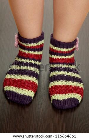 Legs female in striped socks on laminate floor - stock photo