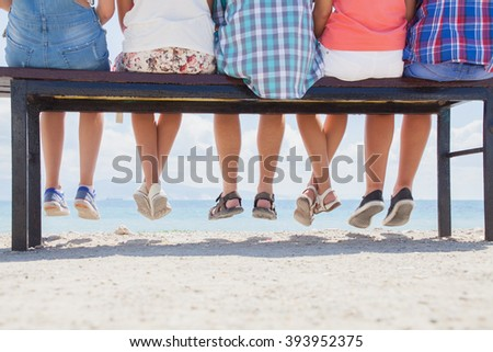 legs  group of teenagers on the bench by the sea. View from the back  - stock photo