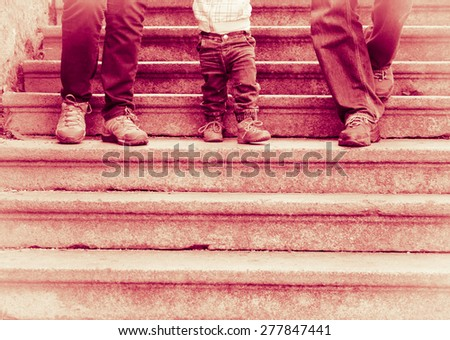 Legs in blue jeans and hiking shoes - Happy family  with two-year-old child walking down old stairs - dark red tinted black and white vintage effect - stock photo