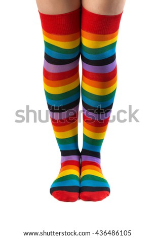 Legs in colored striped socks. Isolate on white. - stock photo