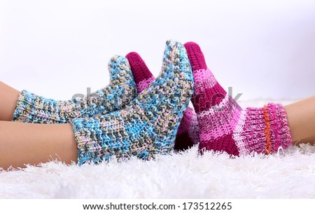 Legs in colorful socks on white carpet background - stock photo