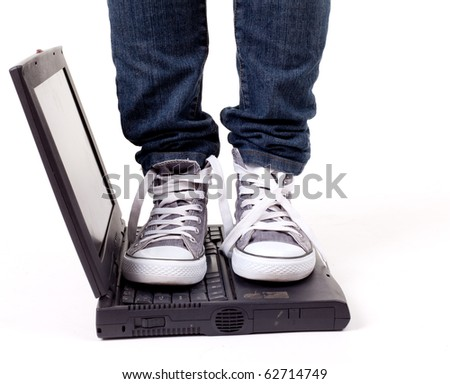 legs in grey gym shoes standing on laptop