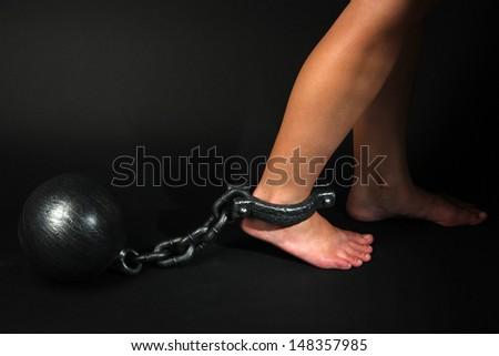 Legs in heavy iron shackles on dark background - stock photo