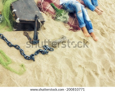 legs in jeans, men and women lying on a plaid blanket on the sand on the beach with a valise, mesh, anchor chain and bouquet, image in the sunny  trendy vintage style - stock photo