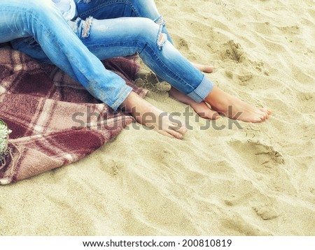 legs in jeans, men and women sitting on a plaid blanket on the sand on the beach, composition shifted, image in the sunny  trendy vintage style - stock photo