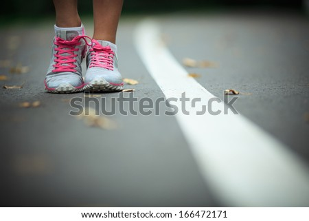 Legs in sneakers on the track - stock photo