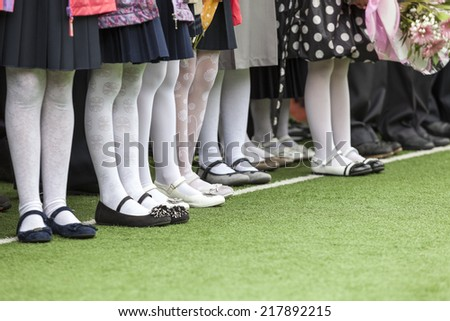 Legs in the boots of little girls standing in line - stock photo