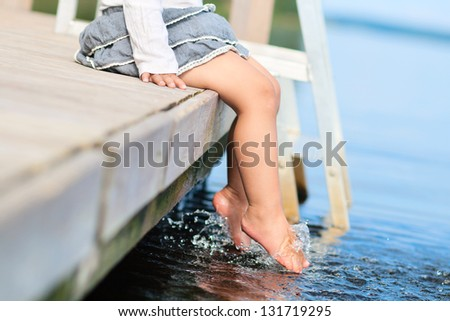 Legs in water of little girl sitting on pier
