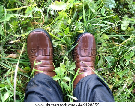 legs in wet boots on grass after rain - stock photo